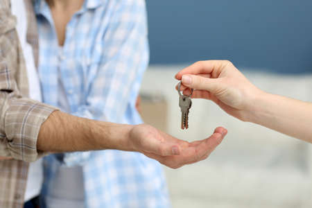 Female hand giving keys from new apartment to male hand on blurred background Stock Photo