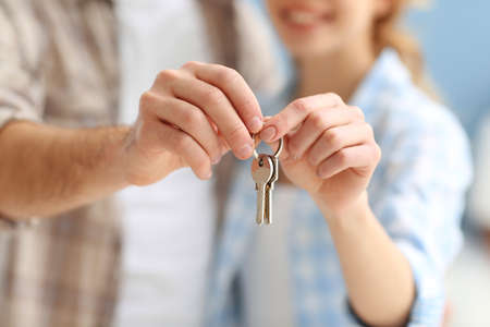 Young happy couple holding keys from their new apartment closeup