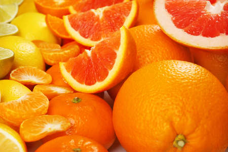 Colorful mixed citrus fruit sorted and lined up in rows with slices and halves, close up Stock Photo