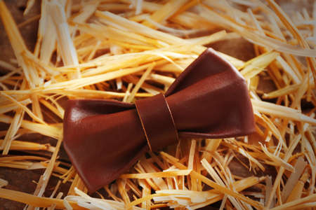Brown leather bow tie on a thatch, close up