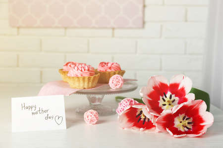 Happy mother day greeting with tulips, cupcakes and present box on white brick wall background