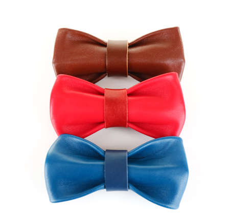 Red, brown and blue leather bow ties lined and isolated on white background Stock Photo