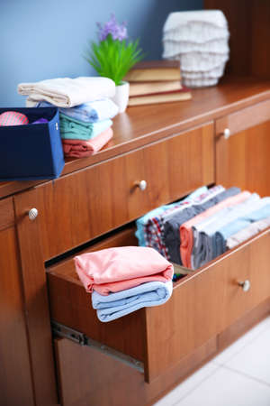 Neatly folded clothes in wooden drawer Stock Photo
