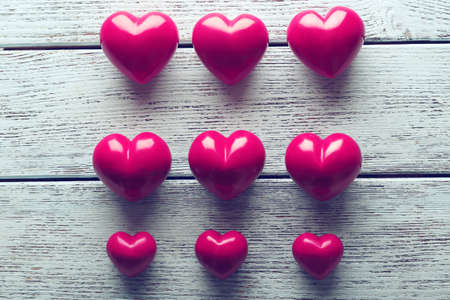Set of red hearts on blue wooden background