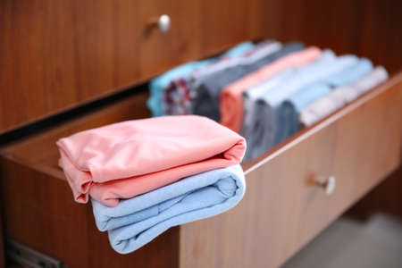 Neatly folded clothes in wooden drawer 스톡 콘텐츠