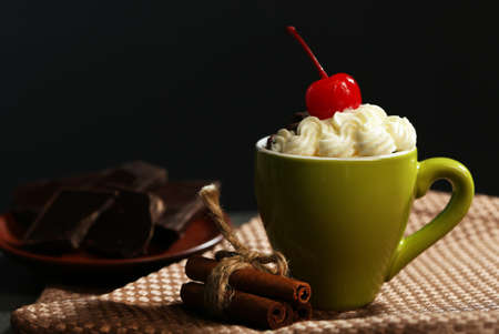 Chocolate cake in a green mug  with whipped cream and a cherry on top, close up
