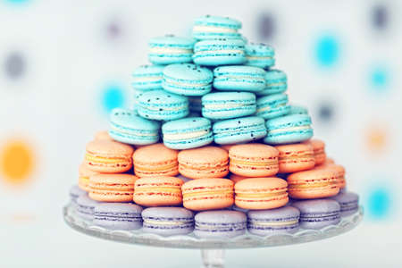 Many varicolored tasty macaroons on glass tray, close up