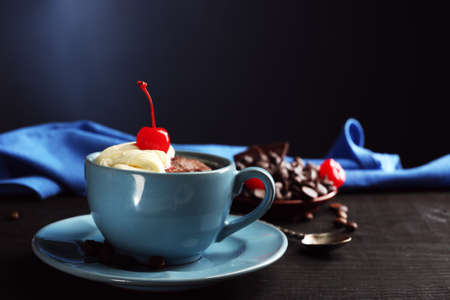 Chocolate cake in a blue mug with a cherry on a dark background, close up Stock Photo