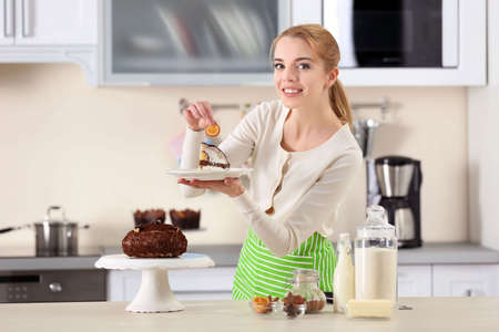 Young woman serving a piece of chocolate cake on a plate Stock Photo
