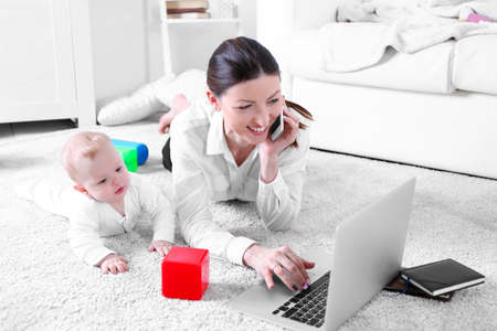 Businesswoman with baby boy working from home using laptop and mobile phone Stock Photo