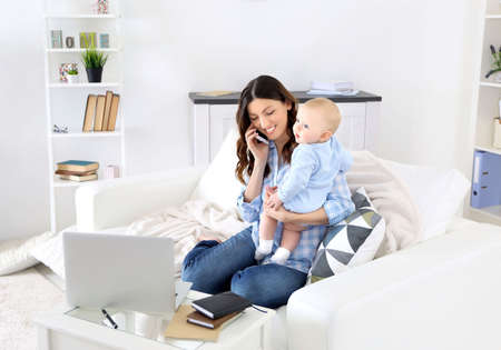 Beautiful woman with baby boy working from home using laptop and mobile phone