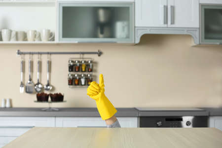 Woman hand in yellow rubber glove gesturing OK (yes) behind kitchen counter Stock Photo