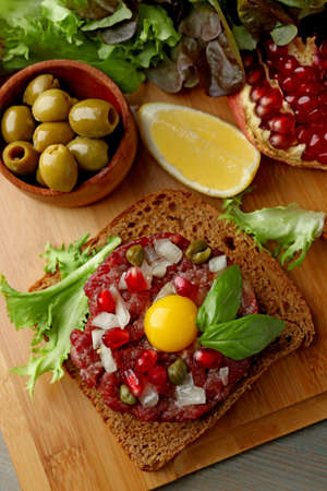 Beef tartare served on a wooden board, top view Stock Photo