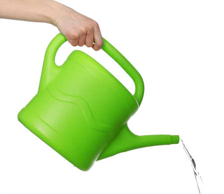 Female hand pouring from green plastic watering can, isolated on white background