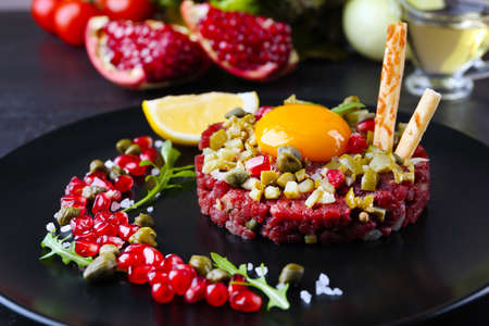 Beef tartare served in a round black plate, close up Stock Photo