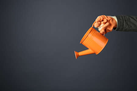 Hand holding orange metal watering can on grey background