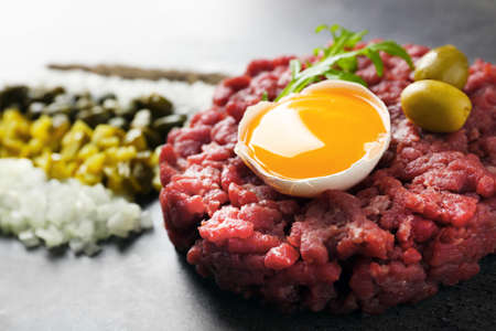 Beef tartare served with a set of ingredients on a grey surface, close up Stock Photo