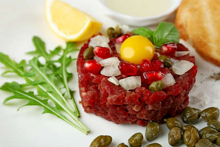 Beef tartare served on a white plate, close up