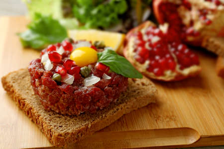 Beef tartare served on a wooden board, close up Banco de Imagens