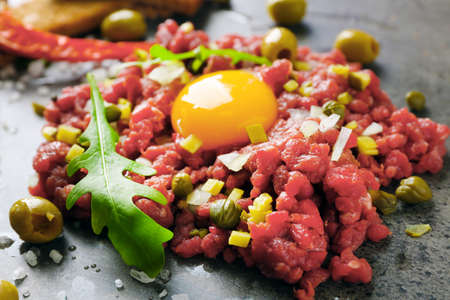 Beef tartare served with croutons on a grey surface, close up