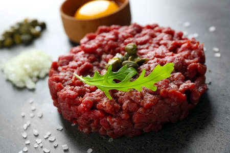 Beef tartare served with an egg yolk on a grey surface, close up
