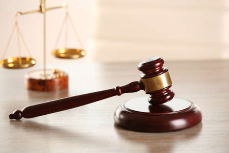 Gavel and scales of justice on wooden table indoors Stock Photo
