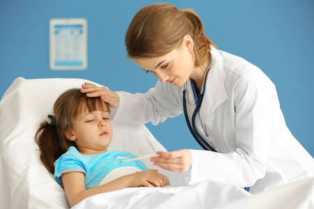 Doctor checking little girls temperature with a thermometer