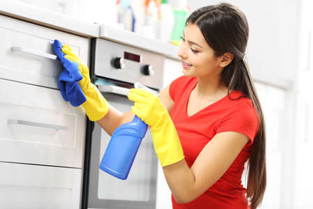 Beautiful woman in protective gloves cleaning kitchen cabinet