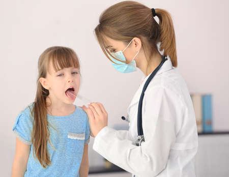Doctor examining little girl's throat 写真素材