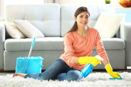 Beautiful woman in protective gloves cleaning carpet with brush and spray Stock Photo