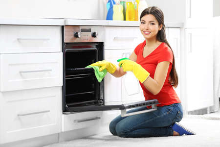 Beautiful woman in protective gloves cleaning oven with rag and spray