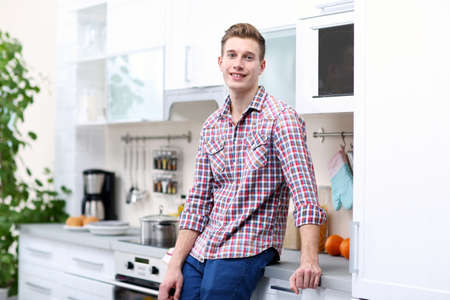 Happy handsome man in bright kitchen