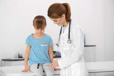 Doctor examining little girl with a reflex hammer in office Archivio Fotografico