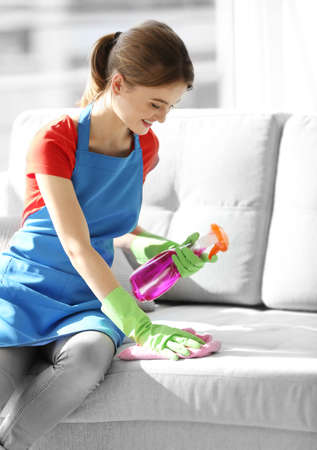 Cleaning concept. Young woman cleans sofa in the room