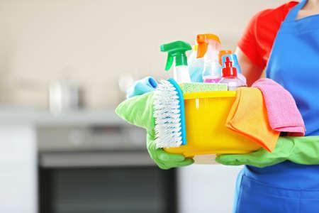 Concepto de limpieza. Mujer joven tiene cuenca con líquidos de lavado y trapos en las manos, de cerca Foto de archivo