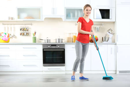 Cleaning concept. Young woman washing floor on the kitchen Stock Photo