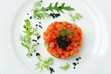 Delicious salmon tartare with black caviar on white plate