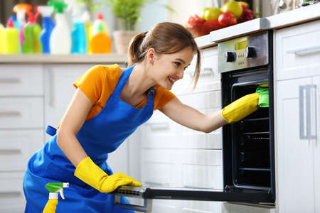 Concepto de limpieza. Mujer lava un horno en la cocina