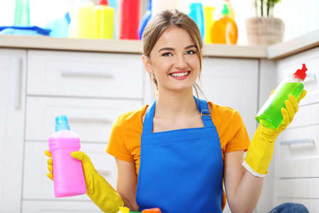 Cleaning concept. Young woman sitting on the floor with cleaning fluids Stockfoto