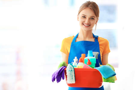 Cleaning concept. Young woman holds plastic basin with washing fluids and rags in hands Stock Photo