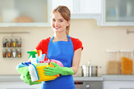 Concepto de limpieza. Mujer joven sostiene cuenca con líquidos de lavado y trapos en las manos