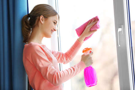 Cleaning concept. Young woman washing window, close up