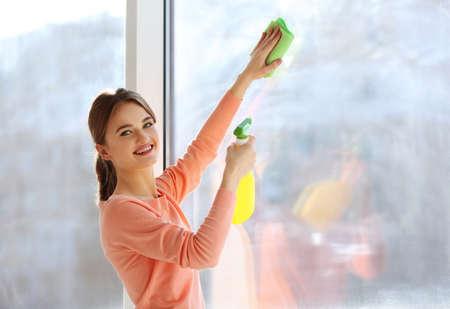 Concepto de limpieza. Mujer joven, lavado, ventana, cicatrizarse