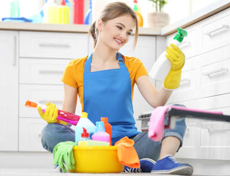 Cleaning concept. Young woman sitting on the floor with cleaning fluids Stock Photo