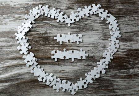 Heart shape puzzles on wooden background