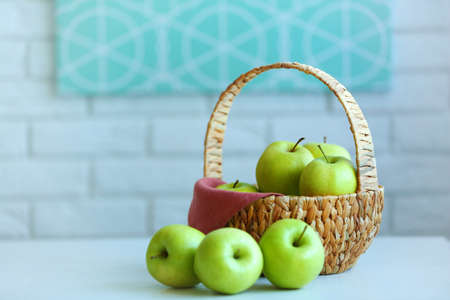 Ripe green apples in basket on a kitchen table Stock Photo