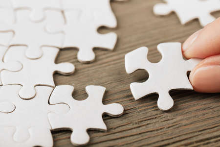 Woman playing with jigsaw puzzle on wooden table