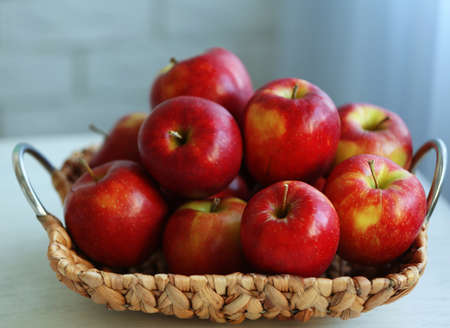 Ripe red apples in wicker basket on a kitchen table