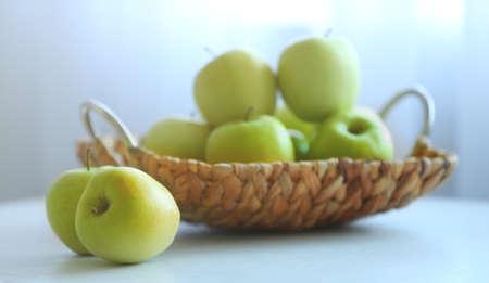 Ripe green apples in a wicker basket on a kitchen table