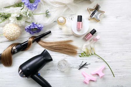 밝은 나무 배경에 꽃, 이발사 장비 및 도구와 머리카락의 가닥